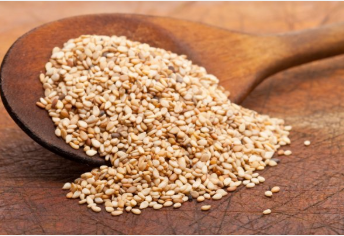 Sesame seeds being spooned onto a wooden counter
