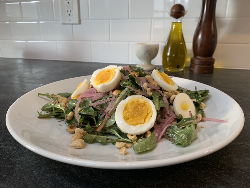 Completed dandelion salad with hazelnuts and dijon vinaigrette