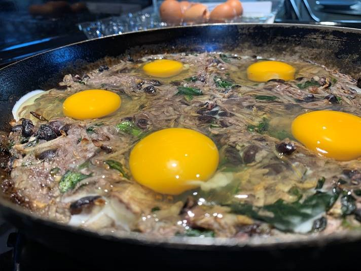 Eggs being fried on black bean hash on a stove top