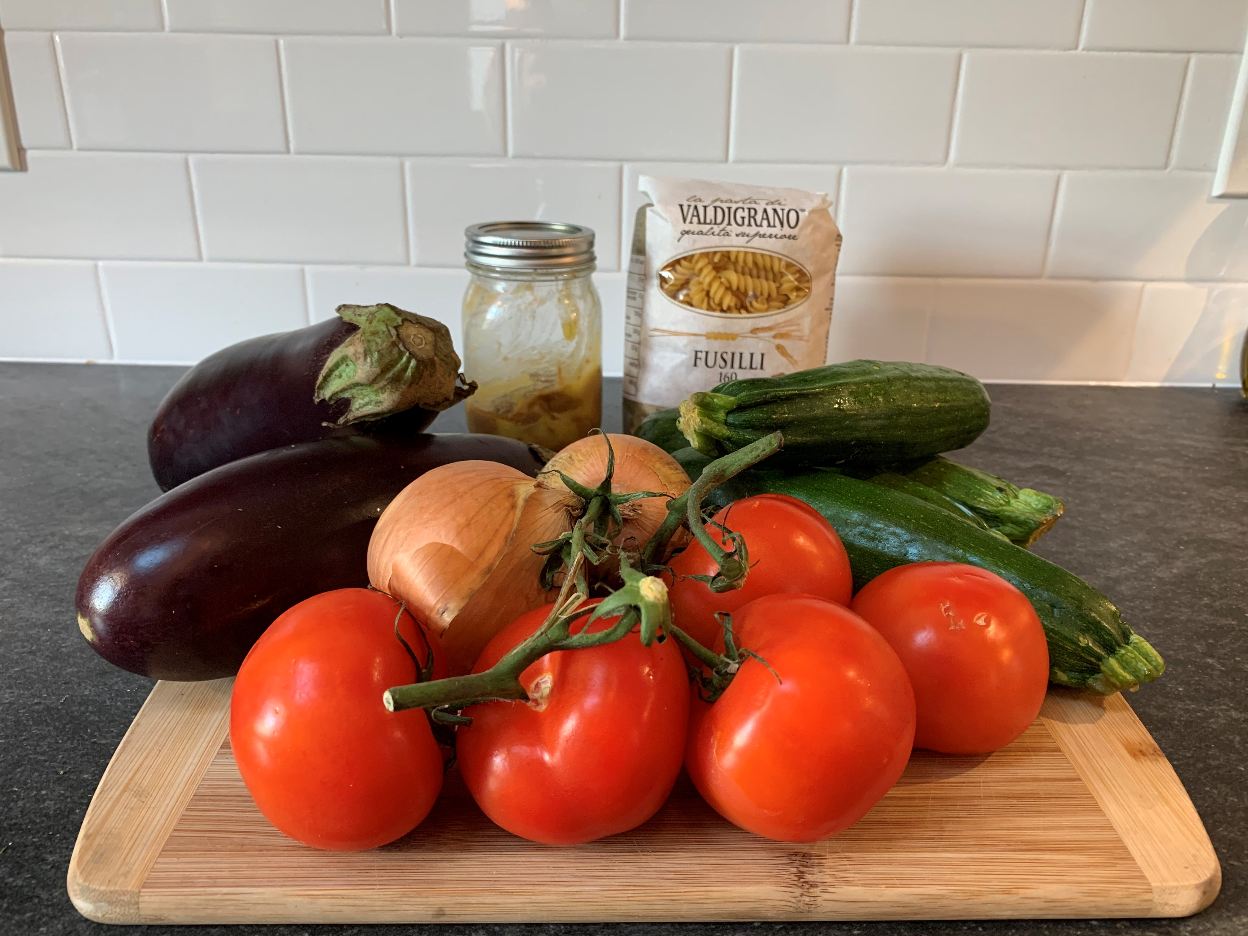 A kitchen counter with various vegetables and the ingredients for ratatouille pasta