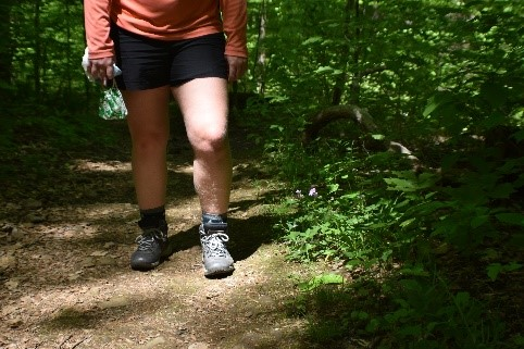 A person in a salmon-colored shirt and shorts hiking