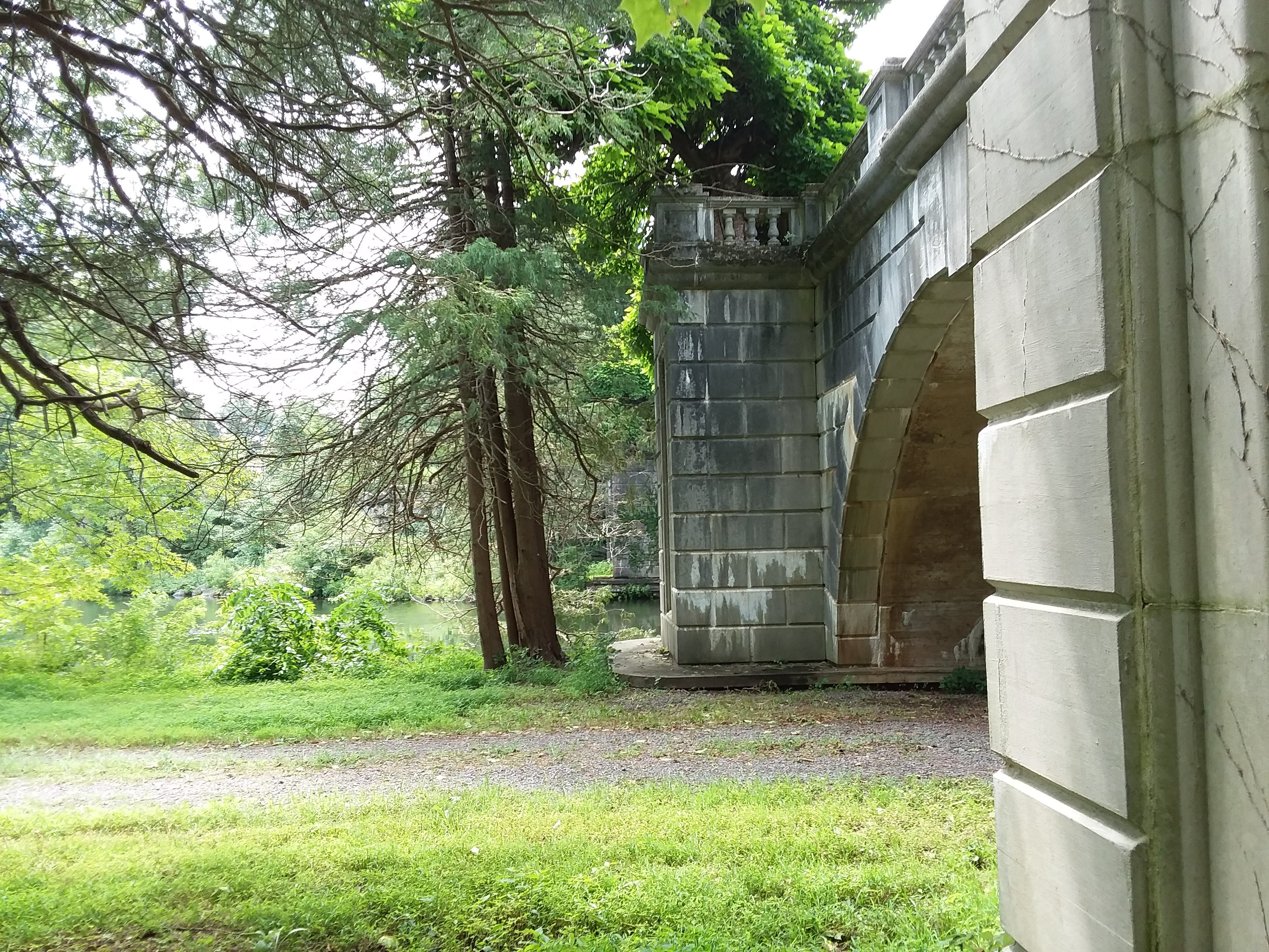 A stone bridge with overlooking a body of water obscured by trees and their overhanging branches